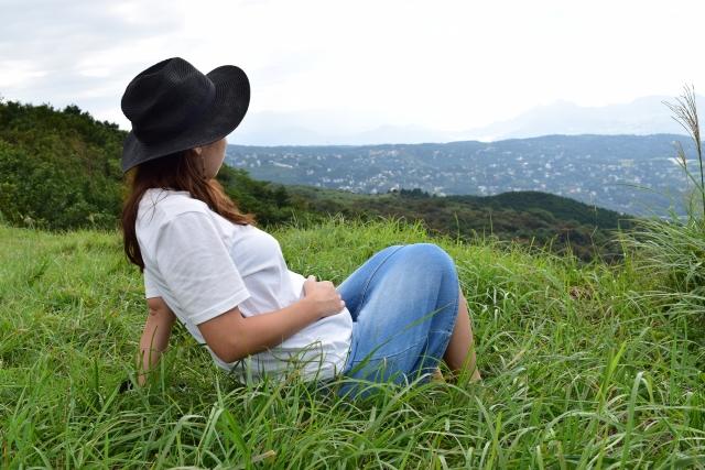 草原で横たわる妊娠中の女性