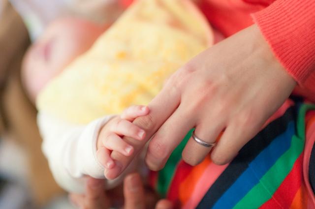 お昼寝中の赤ちゃんの指で遊ぶママ
